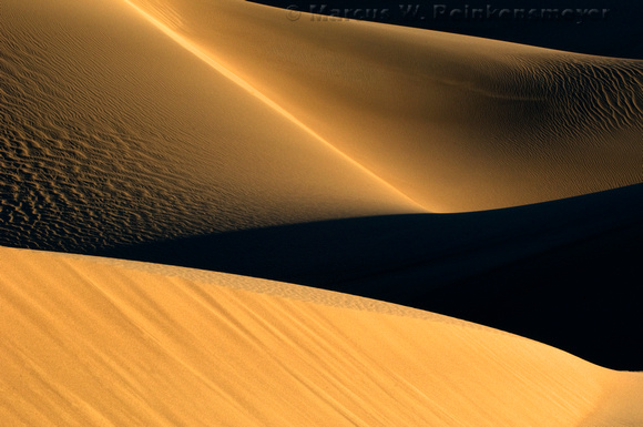 Warm sunlight and long shadows create abstract images at the Mesquite Flat Dunes in Death Valley National Park, California.