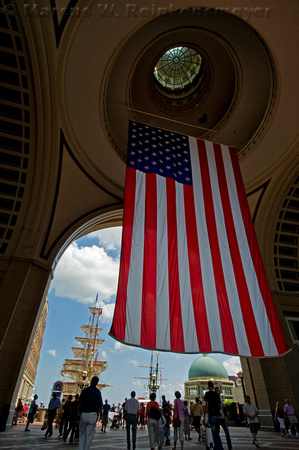 American flag hanging proudly in building atrium, with tall ships in the Boston Harbor.