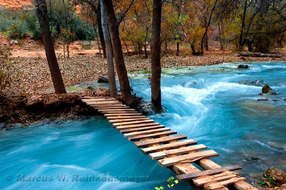 Wooden footbridge crossing blue waters, downstream of Havasu Falls, Arizona.