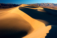 Dramatic sand dune formations flanked by the Panimint Mountains, at Mesquite Flat Dunes in Death Valley National Park.