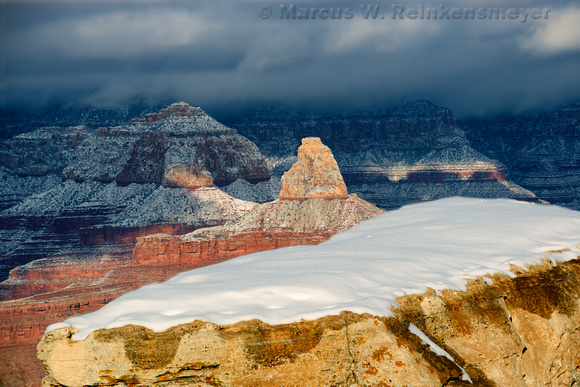 Snow covered bolder and sunlit buttes at Mather Point, Grand Canyon National Park, Arizona.