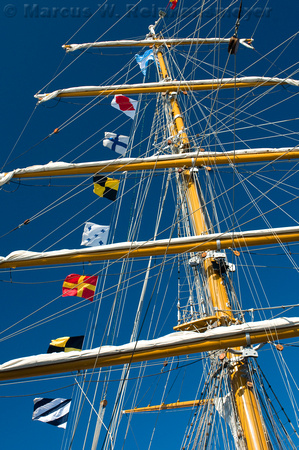Tall ship masts with international flags, docked in Boston Harbor.
