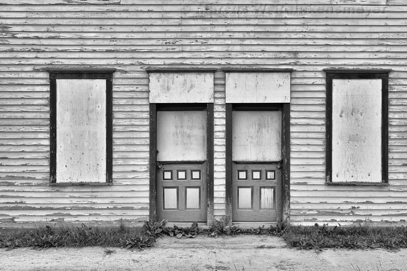 Boarded windows and weathered siding at an abandoned building in historic SIlveton, Colorado.